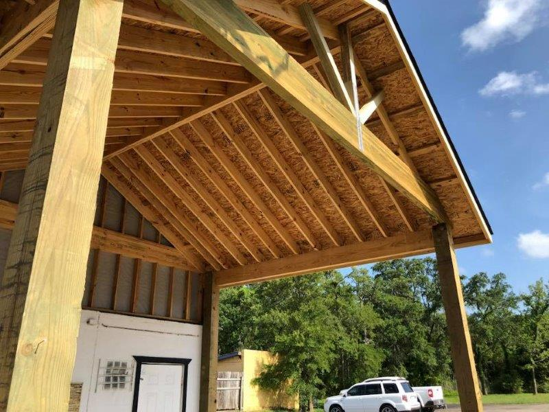 A new custom build carport with high pitched and shingled roof.